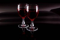 Two glasses of red wine on dark background