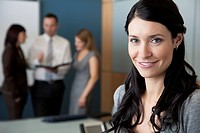 Businesswoman smiling at the camera in a conference room with her co_workers in the background.