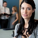 Businesswoman looking at the camera in a conference room with her co_workers in the background.