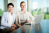 Two businesswoman smiling while sitting at a conference table.
