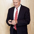 Mature businessman smiles while texting on a cellphone.