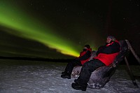 Young couple, woman and man, sitting in a wooden chair, watching swirling northern polar lights, Aurora borealis, green, near Whitehorse, Yukon Territ...