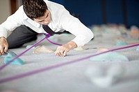 Businessman in a shirt and tie ascending a climbing wall.