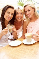 Three Women Enjoying Cup Of Coffee In CafŽ