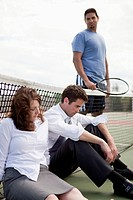 Businessman and businesswoman sit exhausted on a tennis court.