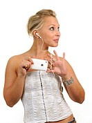 Young woman holding a white Apple iPhone, listening to music with earphones