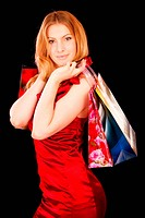 Beautiful girl in red dress is engaged in shopping, it is isolated on black background.