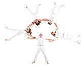 People lying on the floor making a circle and wearing white clothes – isolated