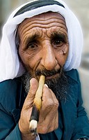 A Bedouin man smoking a traditional cigar in the old city of Jerusalem