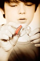 Boy looking at a hearing aid device