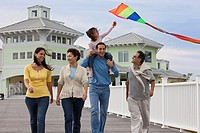 Family walking on boardwalk with kite