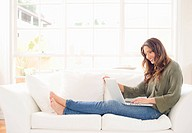 Hispanic woman sitting on sofa using laptop
