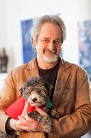 Smiling Caucasian man holding dog