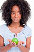 Young curly woman holding a green apple in her hands against a white background