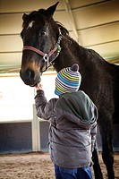 Photo essay at EQUISENS, a therapeutic riding centre in Asniere_les_Dijon France. Hippotherapy session with a child having autistic disorders.