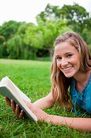Happy student lying on the grass in the countryside while holding a book