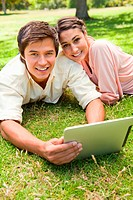 Two friends looking straight ahead as they use a tablet together while lying down on the grass