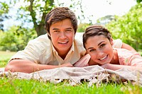 Man and a woman smiling as they lie on their front on top of a grey blanket together