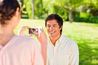 Using a camera, the woman takes a photo of her friend smiling in the park