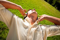 Man singing while using headphones to listen to music as he lies in grass