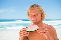 Smiling man holding a piece of a watermelon while standing in front of the ocean