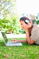 Side view of a young woman with a laptop and headphones on the lawn