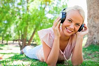 Smiling young woman lying on the grass while listening to music