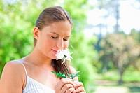 Young woman smelling on a flower in the park