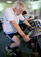 Gym exercise. Man and woman using exercise bikes in a leisure centre´s fitness area. Exercise bikes are used for cycling, a form of aerobic exercise t...