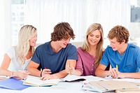 A group of students laughing together as they all study the work