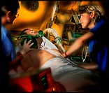 Intensive care. Nurses conduct physiotherapy on the lungs of a man in a hospital intensive care unit. The patient has been taken off the respirator at...