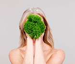 Mature woman holding plant in front of face