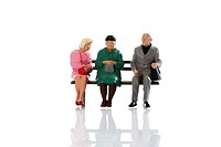 Miniature figures, older persons, seniors and a young woman sitting on a bench