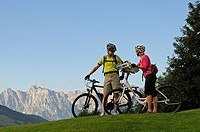 A couple riding electric bicycles, Wilder Kaiser mountain at the back, Reit im Winkl, Chiemgau, Upper Bavaria, Bavaria, Germany, Europe