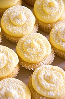 A tray of lemon cupcakes with icing and icing sugar