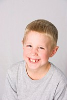 A young blond boy smiles widely at the camera against a grey background