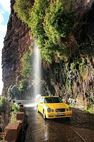 Taxi driving through waterfall at the old coastal road, also called the car washing street, Madeira, Portugal, Europe