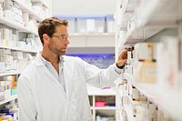 Pharmacist browsing medicines on shelf