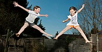 Smiling girls jumping for joy outdoors