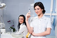 Attractive woman dentist with medical syringe and smiling patient in the dental clinic