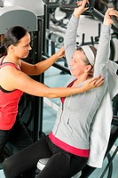 Senior woman at fitness center with trainer