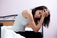This picture shows a young caucasian woman with brown hair as she sits on her bed feeling ill or sick, tired or anxious