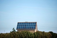 A house with solar panels on the roof seen in the belgian countryside