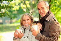 Middle_aged couple drinking coffee in park