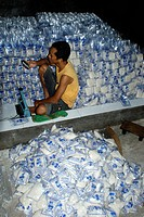 Young man surrounded by clear plastic packets of salt checks his mobile phone in a small salt iodizing business Sakra Lombok Timur NTB Indonesia