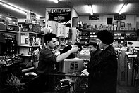 An Italian_American woman with her father buying a radio alarm in a shop in Brooklyn. New York, March 1956