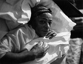 An elderly African American woman posing between the sheets of a Harlem house. New York, February 1956