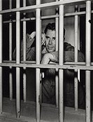 Actor Glenn Ford in ´Young Man with Ideas´. Glenn Ford,as Maxwell Webster, is standing behind guardhouse´s bars.1952.