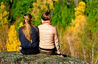 Two girls sitting on a rock