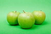 Ripe green apples with water drops on green background
